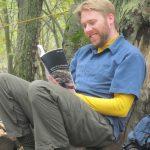 Thomas Peace reading a book under a tree